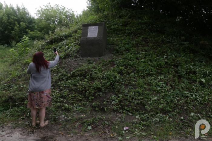 Письменниця Ганна Гороженко фотографує пам'ятну табличку